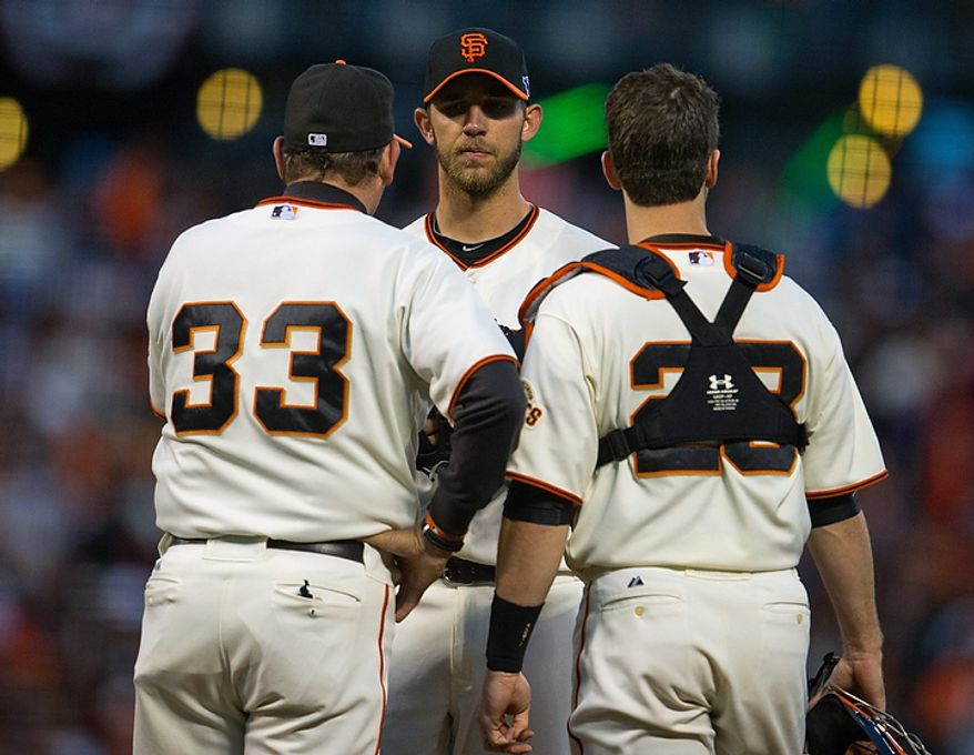 San Francisco Giants pitching coach Dave Righetti (33) visits starting pitcher Madison Bumgarner (40) on the mound along with catcher Buster Posey (28) during Game 1 of the National League baseball championship series against the St. Louis Cardinals, Sunday, Oct. 14, 2012, in San Francisco. (AP Photo/The Sacramento Bee, Jose Luis Villegas)