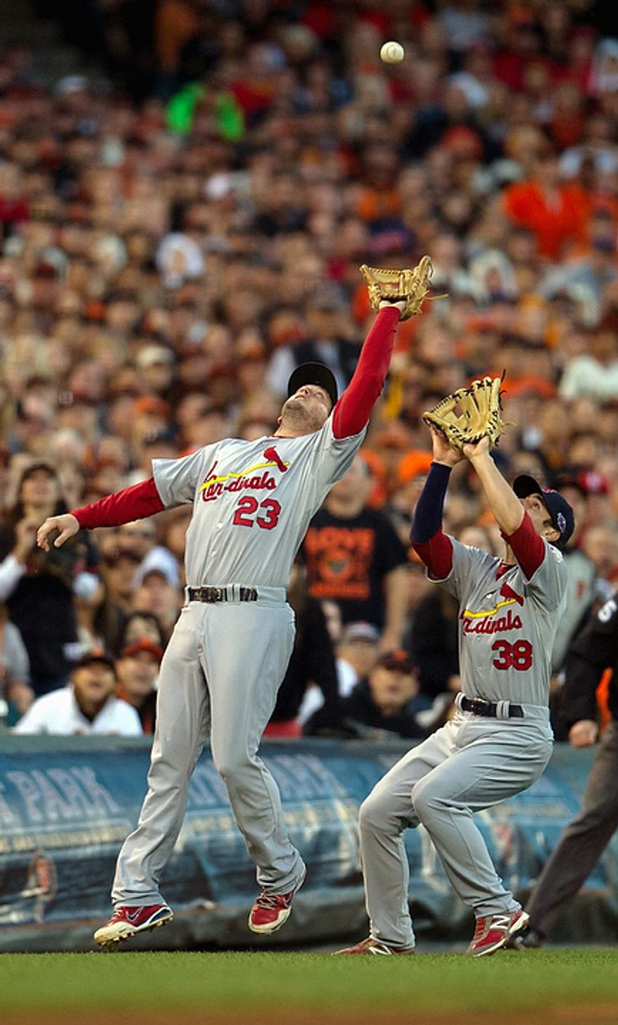St. Louis Cardinals third baseman David Freese (23) and shortstop Pete Kozma try and play the same foul ball from San Francisco Giants' Angel Pagan during Game 1 of the National League baseball championship series, Sunday, Oct. 14, 2012, in San Francisco. (AP Photo/The Sacramento Bee, Jose Luis Villegas)