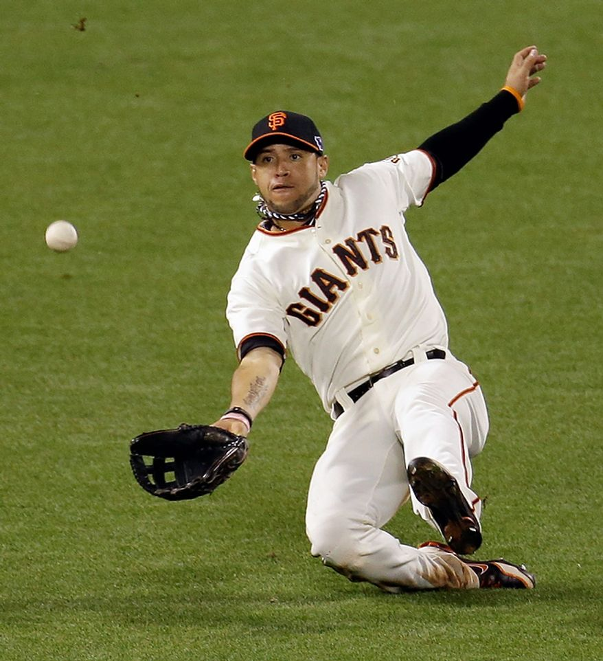 San Francisco Giants' Gregor Blanco makes a sliding catch on a ball hit by St. Louis Cardinals' Skip Schumaker during the sixth inning of Game 1 of baseball's National League championship series Sunday, Oct. 14, 2012, in San Francisco. (AP Photo/Eric Risberg)