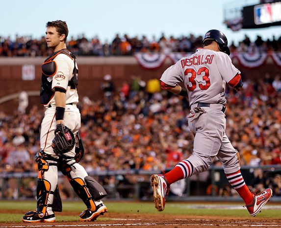 San Francisco Giants catcher Buster Posey walks to the mound as St. Louis Cardinals' Daniel Descalso scores on a double by Pete Kozma during the fourth inning of Game 1 of baseball's National League championship series Sunday, Oct. 14, 2012, in San Francisco. (AP Photo/Ben Margot)