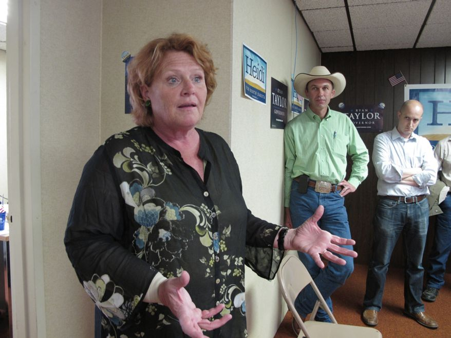 **FILE** Heidi Heitkamp, the North Dakota Democratic candidate for the U.S. Senate, speaks Aug. 11, 2012, during the opening of a North Dakota Democratic campaign office in Dickinson, N.D. At right is Ryan Taylor (with hat), the North Dakota Democratic candidate for governor, and Ryan Nagle, a Democratic campaign staffer. (Associated Press)