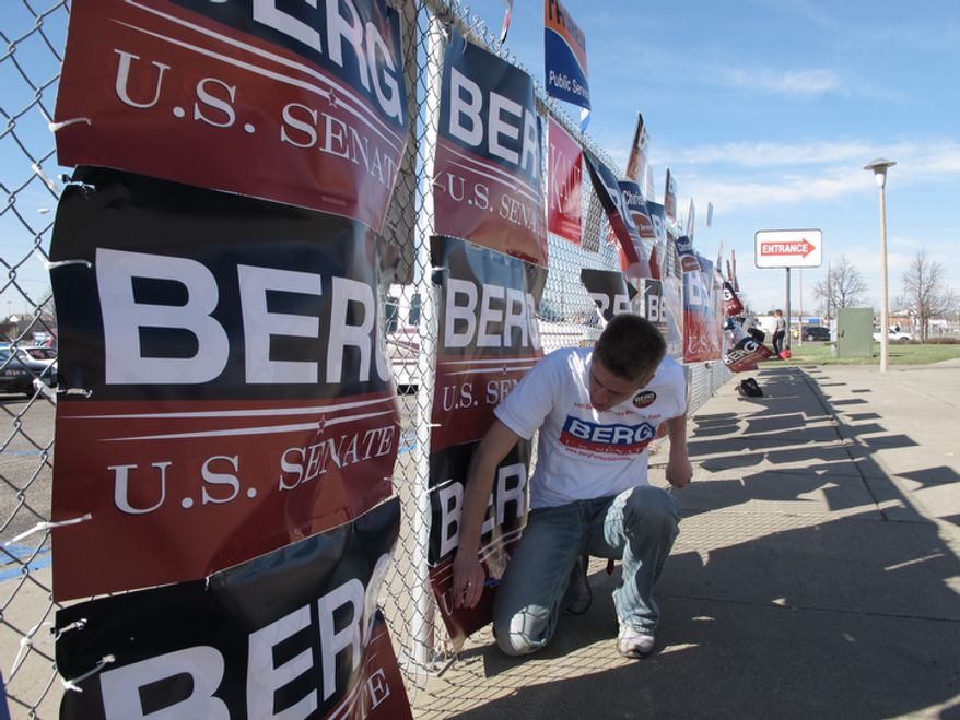 **FILE** A volunteer works to prevent campaign signs supporting the U.S. Senate candidacy of North Dakota Republican U.S. Rep. Rick Berg from blowing away in the wind on March 30, 2012, outside the Bismarck Civic Center in Bismarck, N.D., where North Dakota Republicans are holding their state convention this weekend. (Associated Press)