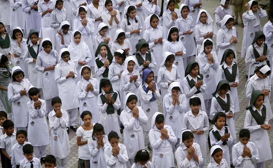 Pakistani schoolgirls pray for the recovery of 14-year-old Malala Yousufzai, who was shot Tuesday by the Taliban for speaking out in support of education for girls, at their schoolyard in Gujranwala, Pakistan, on Monday, Oct. 15, 2012. (AP Photo/Aftab Rizvi)