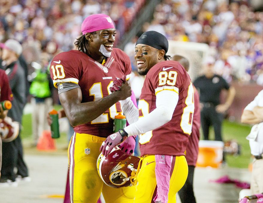 Washington Redskins quarterback Robert Griffin III (10) laughs with wide receiver Santana Moss (89) on the sideline after running a 76 yards for a touchdown to put the Washington Redskins up 38-26 in the fourth quarter as the Washington Redskins play the Minnesota Vikings at FedEx Field, Landover, Md., Sunday, October 14, 2012. (Craig Bisacre/ The Washington Times)