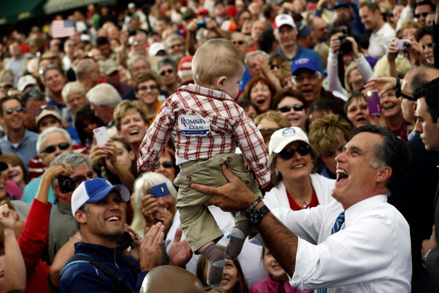 Republican presidential candidate Mitt Romney picks up a baby as he campaigns at The Golden Lamb restaurant in Lebanon, Ohio, on Oct. 13, 2012. (Associated Press)