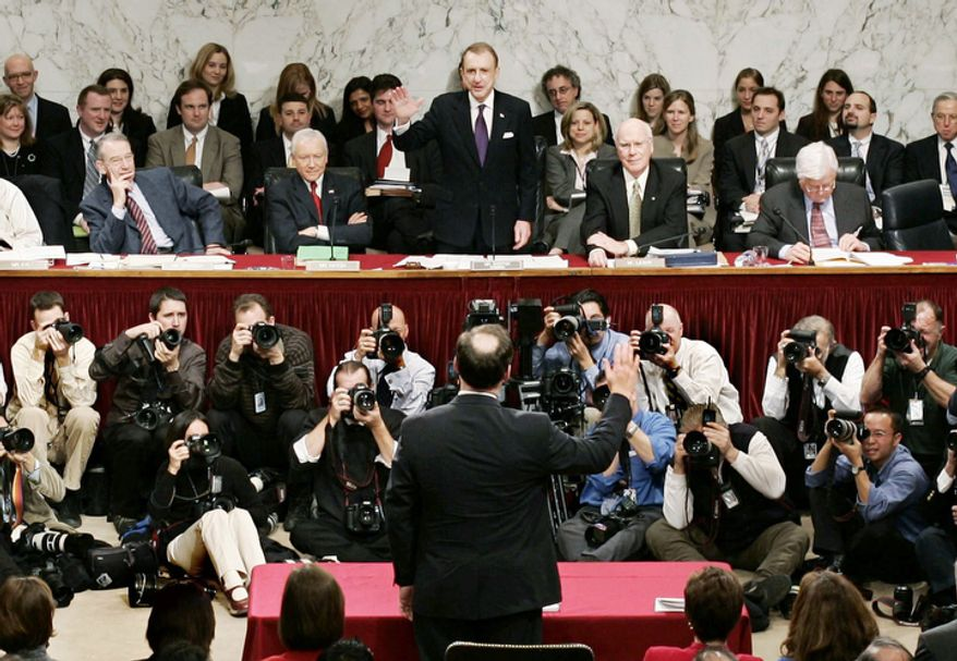 **FILE** Sen. Arlen Specter (center, facing camera), Pennsylvania Republican and Senate Judiciary Committee Chairman, swears in Supreme Court nominee Samuel Alito (back to camera) on Jan. 9, 2006, during his confirmation hearing before the committee on Capitol Hill in Washington. (Associated Press)