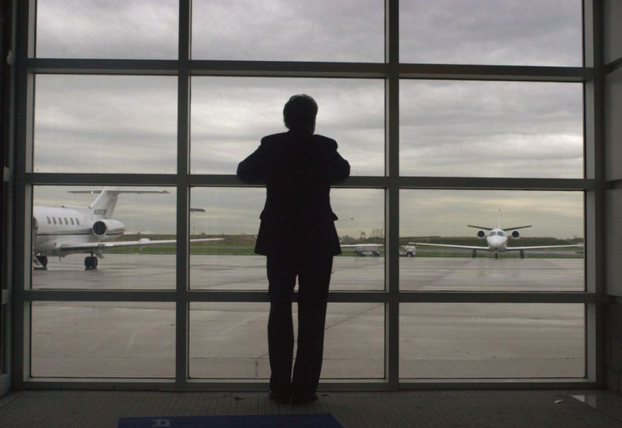 **FILE** Sen. Arlen Specter, Pennsylvania Republican, looks out toward the tarmac at the executive terminal of Philadelphia International Airport on April 26, 2004, as he waits to board a plane while campaigning the day before Pennsylvania's Republican primary. (Associated Press)