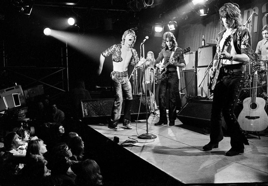 This March 26, 1971 file photo shows British rock and roll band The Rolling Stones during their farewell performance at London's Marquee Club, in London.  The band members are, from left, Mick Jagger, vocals; Mick Taylor, guitar; Keith Richards, guitar; and Charlie Watts, drums. The musician in background is unidentified. Thursday, July 12, 2012, marks 50 years since Jagger played his first gig with the band. Now in their late 60s and early 70s, the band members are celebrating the anniversary by attending a retrospective photo exhibition at London's Somerset House _ and looking to the future by rehearsing for new gigs. (AP Photo, file)