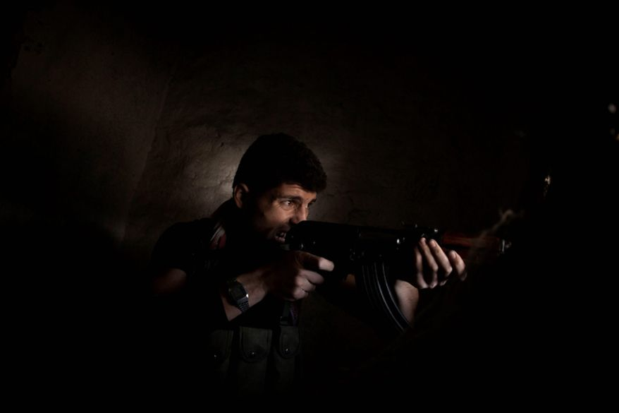 A Free Syrian Army fighter fires his weapon toward government forces (unseen) in the Karmal Jabl district of Aleppo, Syria, on Sunday, Oct. 14, 2012. (AP Photo/Manu Brabo)