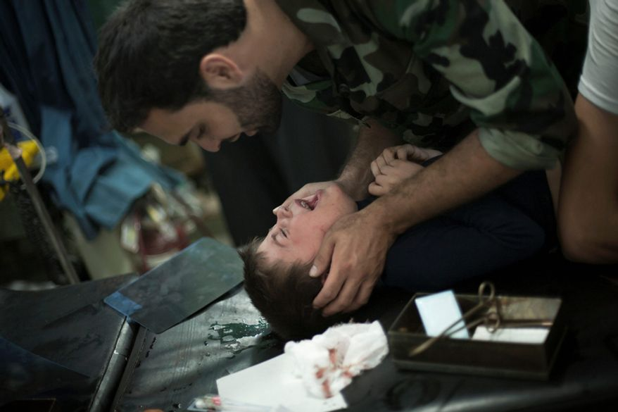 A Free Syrian Army fighter comforts a child wounded by Syrian army artillery shelling, at Dar al-Shifa Hospital in Aleppo, Syria, on Wednesday, Oct. 10, 2012. (AP Photo/ Manu Brabo)