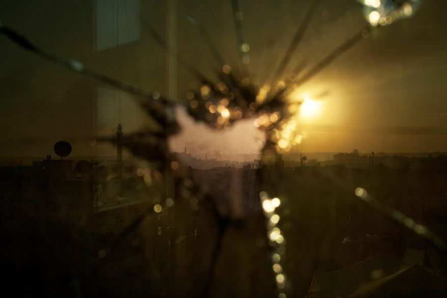 Smoke rises from buildings hit by government forces shelling, as seen through broken glass, in Aleppo, Syria, on Saturday, Oct. 13, 2012. (AP Photo/Manu Brabo)