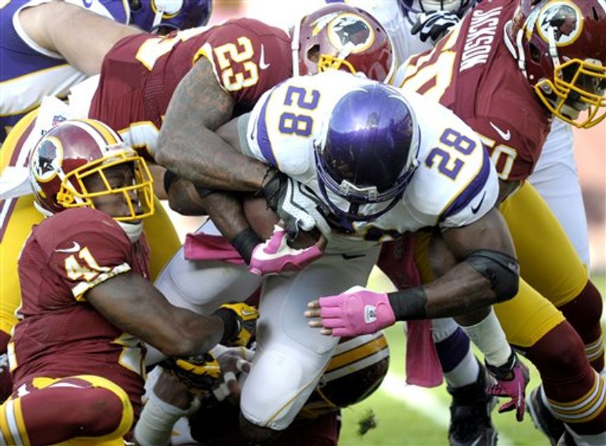 Washington Redskins free safety Madieu Williams (41), cornerback DeAngelo Hall (23), and linebacker Rob Jackson (50), combine to bring down Minnesota Vikings running back Adrian Peterson (28) during the first half of an NFL football game, Sunday, Oct. 14, 2012, in Landover, Md. (AP Photo/Cliff Owen)