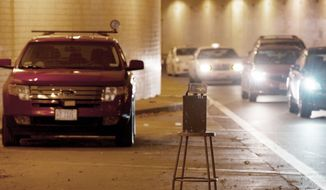 A traffic speed enforcement unit was set up in the Ninth Street tunnel in Northwest on Tuesday. D.C. Council members, citing constituent concerns, are considering lowering the fine from speed cameras to $50 per violation. (Barbara L. Salisbury/The Washington Times)