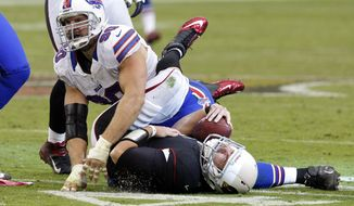 Arizona Cardinals quarterback Kevin Kolb, bottom, is injured after being hit by Buffalo Bills defensive end Chris Kelsay (90) during the second half of an NFL football game, on Sunday, Oct. 14, 2012, in Glendale, Ariz. Kolb left the game and the Bills went on to win 19-16 in overtime. (AP Photo/Rick Scuteri)