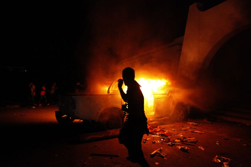**FILE** A Libyan civilian watches one of Ansar al-Shariah Brigades' cars burn, after hundreds of civilians, military and police raided the Brigades base in Benghazi, Libya, in 2012. (Associated Press)