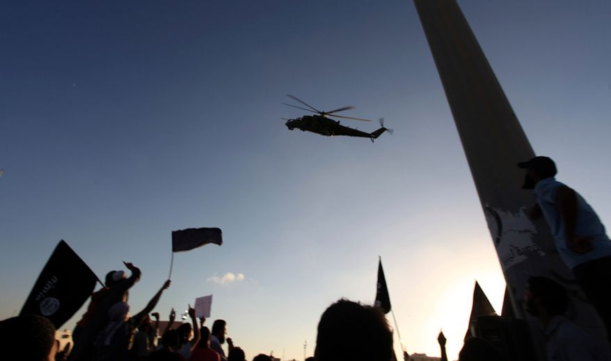 **FILE** A Libyan military helicopter flies Sept. 21, 2012, over a demonstration at Victory Square in Benghazi, Libya, by Ansar al-Shariah Brigades and other Islamic militias. The attack that killed the U.S. ambassador and three other Americans has sparked a backlash among frustrated Libyans against the heavily armed gunmen, including Islamic extremists, who run rampant in their cities. More than 10,000 people poured into a main boulevard of Benghazi, demanding that militias disband as the public tries to do what Libya's weak central government has been unable to. (Associated Press)
