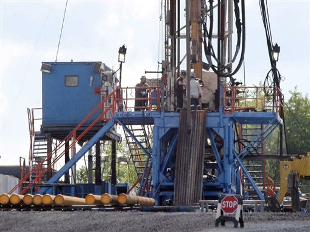 ** FILE ** In this June 25, 2012 photo, a crew works on a gas drilling rig at a well site for shale based natural gas in Zelienopl