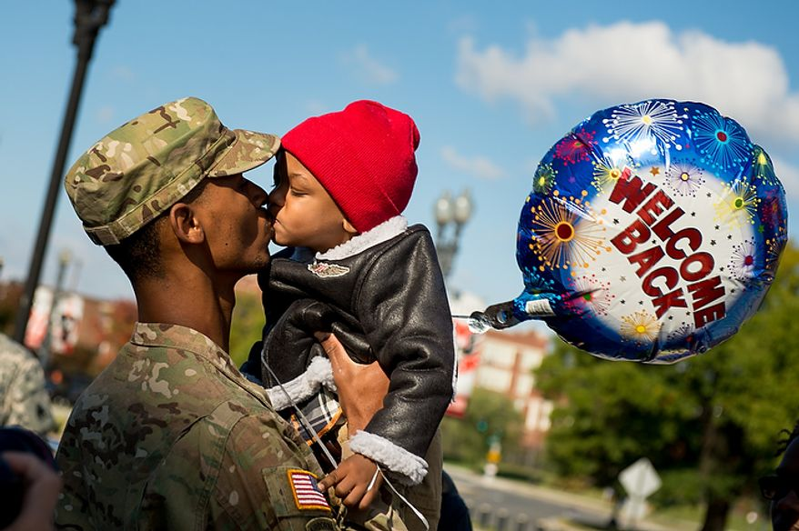 Spc. Marques Turpin, one of the 70 D.C. Army National Guard soldiers with the 273rd military police company returning from Bagram Air Base, Afghanistan after 10 months kisses his son Josiah, 2, following a  welcome home ceremony held in front of the D.C. Armory, Washington, D.C., Tuesday, October 16, 2012. (Andrew Harnik/The Washington Times)