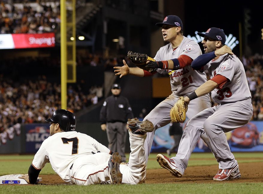 St. Louis Cardinals' Allen Craig (21) and Daniel Descalso (33) argue that San Francisco Giants' Gregor Blanco was tagged out on a play during the eighth inning of Game 2 of baseball's National League championship series Monday, Oct. 15, 2012, in San Francisco. (AP Photo/David J. Phillip)