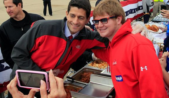 Republican vice presidential candidate, Rep. Paul Ryan, R-Wis. poses for a photo while serving up Montgomery Inn barbeque, Monday, Oct. 15, 2012, at a campaign rally in Cincinnati. (AP Photo/Al Behrman)