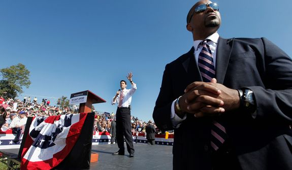 A Secret Service agent stands guard at right as Republican vice presidential candidate, Rep. Paul Ryan, R-Wis. speaks during a rally at Automated Conveyor Systems in Lynchburg, Va., Tuesday, Oct. 16, 2012. (AP Photo/Steve Helber)