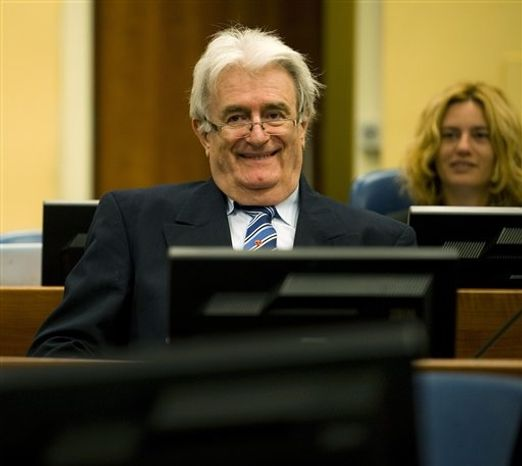 Suspected war criminal and the former leader of Serbs in Bosnia, Radovan Karadzic, left, smiles when taking his seat on the defense bench in the court room to start his defense at the U.N. war crimes tribunal in the Hague in The Hague, Netherlands, Tuesday Oct. 16, 2012. (AP Photo/Robin van Lon