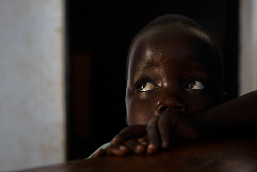 """**FILE** Three-year-old Betty looks up April 27, 2012, at her mother, Adye Sunday, 25, at a center in Gulu, Uganda, set up to help those who have left or fled the Lord's Resistance Army (LRA). Sunday was abducted when she was 13 and forced to be one of the dozens of """"wives"""" of LRA leader Joseph Kony, whom she says is also the father of her two children. (Associated Press)"""