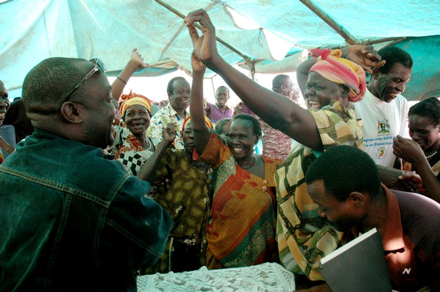 **FILE** Martin Ojul (left), peace delegation for the Leader of Lords Resistance Army (LRA), is welcomed back home Nov. 7, 2007, after 21 years by relatives at Koch Goma in Amuru, a district in northern Uganda. (Associated Press)