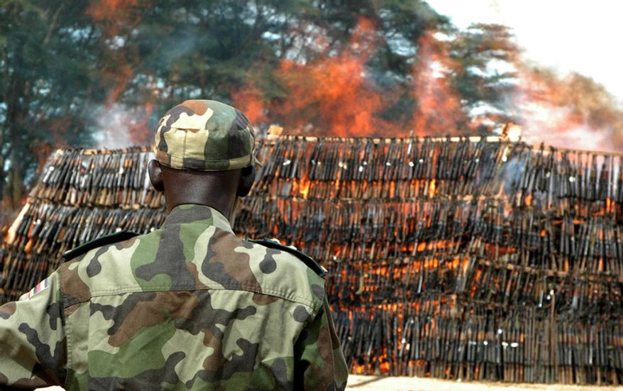 **FILE** Soldiers of the Uganda Peoples Defence Army burn a heap of about 3500 confiscated illegal arms recovered from Lords Resistance Army (LRA) rebels' caches and robbers throughout the country on Oct. 5, 2009, in Kampala, Uganda. The arms ranged from AK-47s to machine guns. (Associated Press)