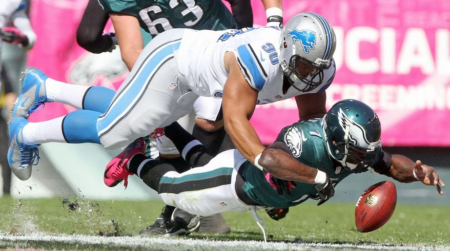 Detroit Lions defensive tackle Ndamukong Suh (90) comes down on Philadelphia Eagles Michael Vick as they chase a ball during the NFL game in Philadelphia Sunday, Oct. 14, 2012. (Andre L. Smith/The News Journal (AP Photo/The Wilmington News-Journal, )