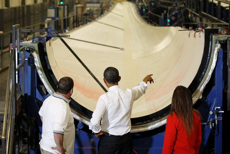 President Obama gets a look at a wind turbine blade with TPI Composites workers Larry Crady and Dajeane Spencer during a May 2012 tour of the plant in Newton, Iowa. (Associated Press) **FILE**