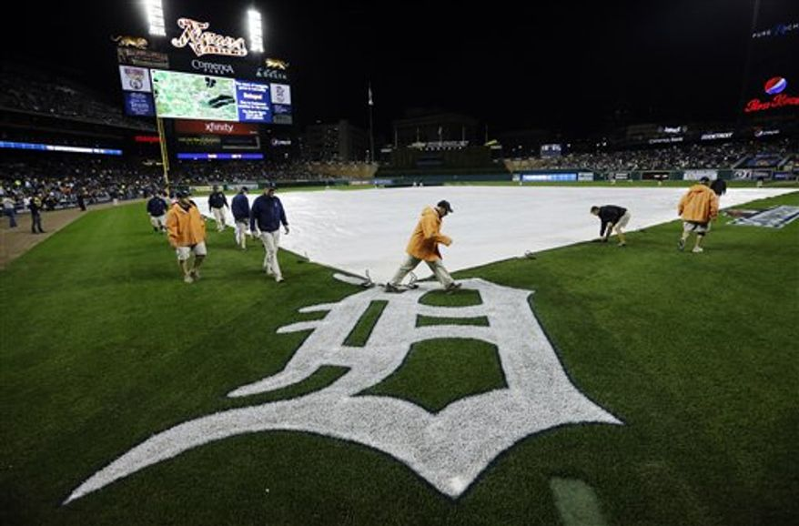 Grounds crew members cover the field during a rain delay at Game 4 of the American League championship series between the Detroit Tigers and New York Yankees Wednesday, Oct. 17, 2012, in Detroit. The game was postponed. (AP Photo/Matt Slocum)