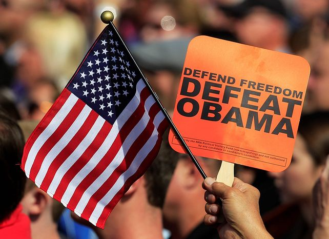 "A supporter of Republican presidential candidate Mitt Romney holds an American flag and a ""Defeat Obama"" sign during a Romney rally at Tidewater Community college in Chesapeake, Va., on Oct. 17, 2012. (Associated Press)"