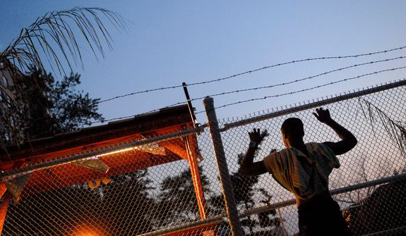A young man who did not want to give his name leans on the barbed wire topped fence and watches a press conference at the Robert L. Yeldell Towers, to denounce culture of gun violence in southeast Washington D.C., Tuesday, August 12, 2008. (Rod Lamkey Jr/The Washington Times)