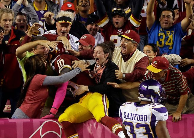 Washington Redskins quarterback Robert Griffin III (10) celebrates with fans after running away from Minnesota Vikings safety Jamarca Sanford (33) for a 76-yard touchdown during the second half of an NFL football game, Sunday, Oct. 14, 2012, in Landover, Md. (AP Photo/Pablo Martinez Mon
