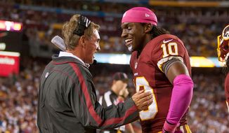 Washington Redskins quarterback Robert Griffin III (10) laughs with Washington Redskins head coach Mike Shanahan on the sideline after running a 76 yards for a touchdown to put the Washington Redskins up 38-26 in the fourth quarter as the Washington Redskins play the Minnesota Vikings at FedEx Field, Landover, Md., Sunday, October 14, 2012. (Craig Bisacre/ The Washington Times)