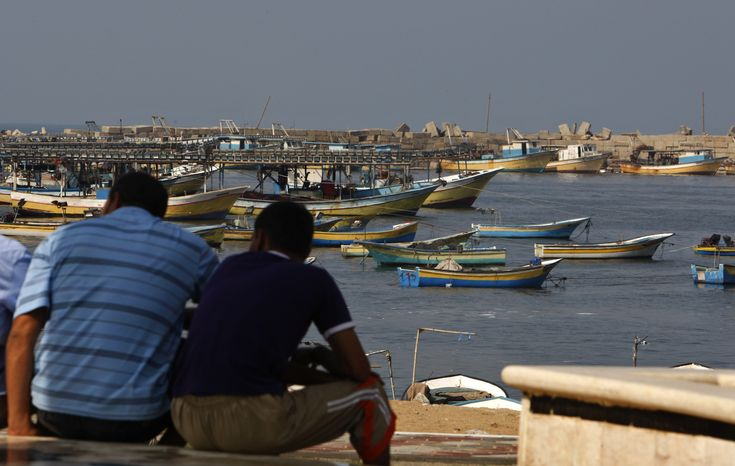 **FILE** Palestinians sit by the port in Gaza City on Oct.