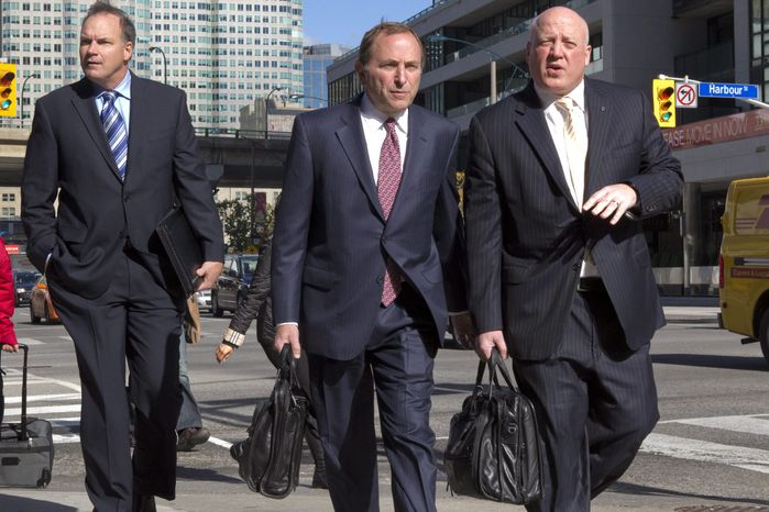 NHL commissioner Gary Bettman, center, arrives with deputy commissioner Bill Daly, right, as the NHL and its locked-out player resume negotiations in Toronto on Wednesday Oct. 16, 2012. (AP Photo/The Canadian Press, Chris Young)