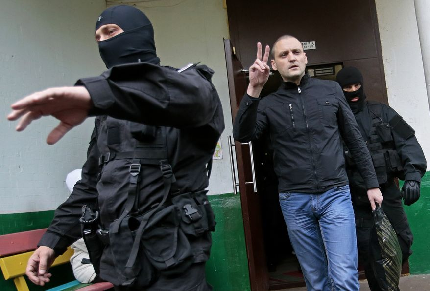 Russian opposition leader Sergei Udaltsov (center) gestures as masked police officers take him for questioning in Moscow on Wednesday, Oct. 17, 2012. In a new sign of a widening crackdown on Russia's opposition, investigators have opened a criminal probe against Mr. Udaltsov and several other activists for allegedly plotting mass riots. (AP Photo/Mikhail Metzel)