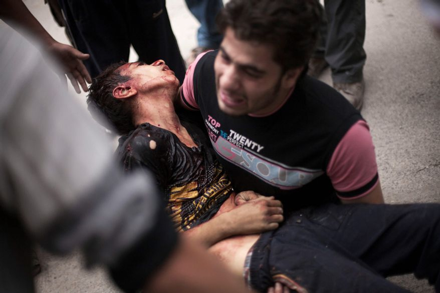 **FILE** A Syrian man cries Oct. 11, 2012, near Dar al-Shifa hospital in Aleppo, Syria, while holding the body of his brother, who killed by Syrian Army shelling. (Associated Press)