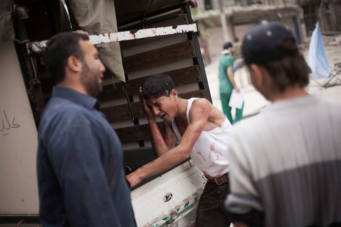 **FILE** A Syrian youth cries Oct. 11, 2012, outside Dar al-Shifa hospital in Aleppo, Syria, while standing next to the truck holding the body his brother, who was killed by Syrian Army shelling. (Associated