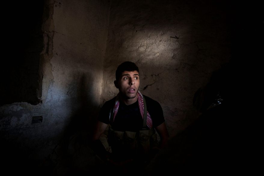 **FILE** A Free Syrian Army fighter sits Oct. 14, 2012, in a storage room in the Karmal Jabl district of Aleppo, Syria. (Associated Press)