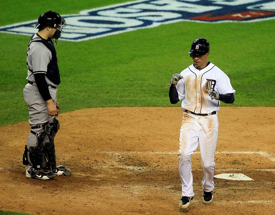 Detroit Tigers' Quintin Berry reacts after scoring on a hit by Miguel Cabrera in front of New York Yankees' Russell Martin in the fifth inning during Game 3 of the American League championship series Tuesday, Oct. 16, 2012, in Detroit. (AP Photo/Carlos Osorio)