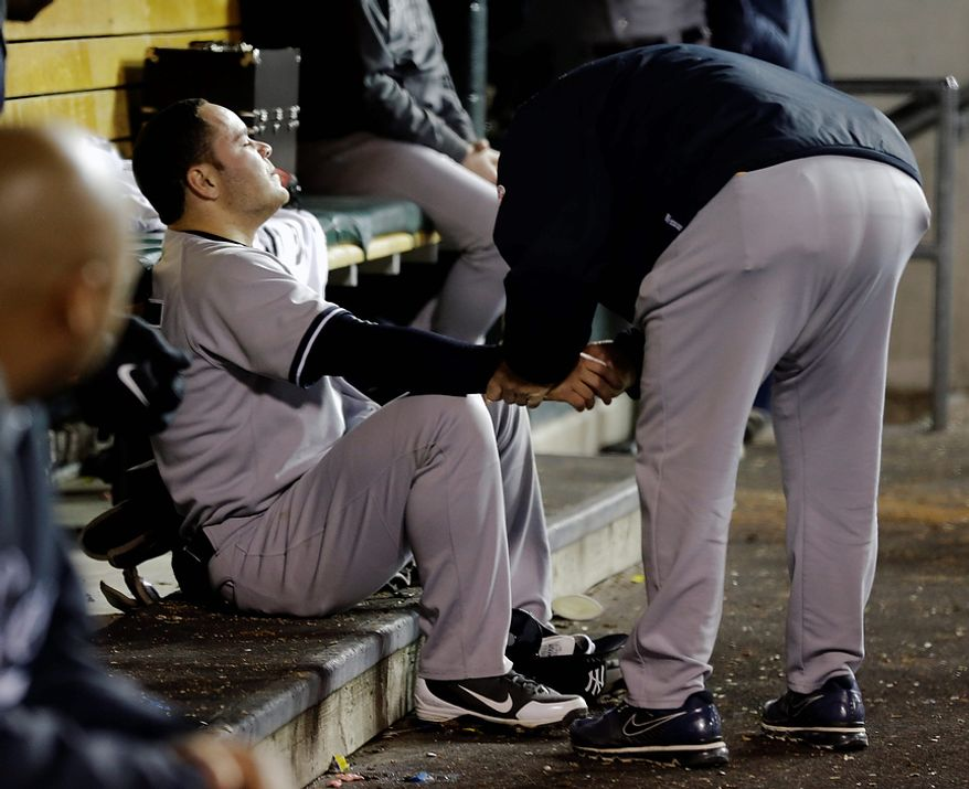 A trainer works on New York Yankees' Russell Martin during Game 3 of the American League championship series against the Detroit Tigers Tuesday, Oct. 16, 2012, in Detroit. (AP Photo/Paul Sancya )
