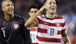 United States forward Clint Dempsey (8) and goalkeeper Tim Howard (1) celebrate their 3-1 win over Guatemala in their World Cup qualifying soccer match in Kansas City, Kan., Tuesday, Oct. 16, 2012. (AP Photo/Reed Hoffmann)