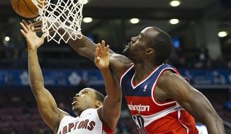 Toronto Raptors guard Kyle Lowry, left, gets stopped by Washington Wizards center Emeka Okafor, right, during the first half of their preseason NBA game, Wednesday, Oct. 17, 2012, in Toronto. (AP Photo/The Canadian Press, Nathan Denette)
