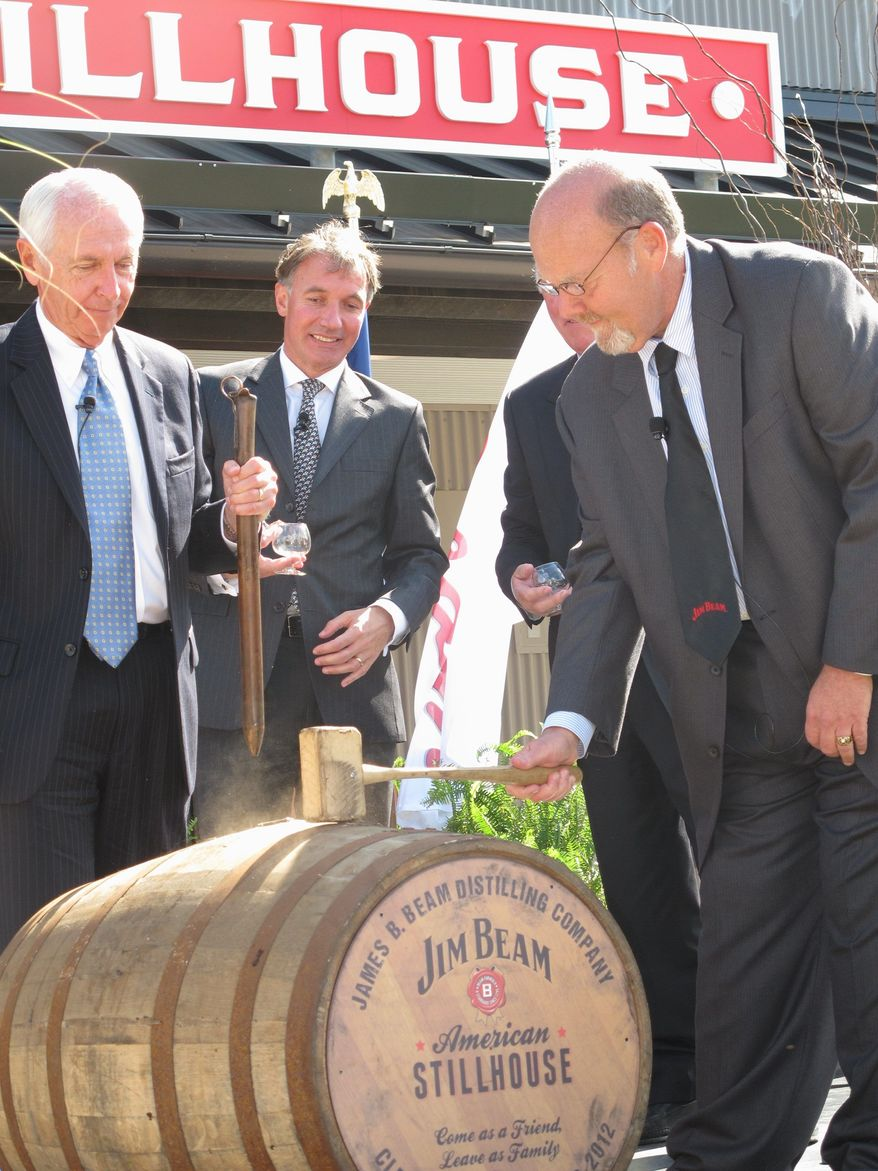 This Oct. 3, 2012 photo shows Jim Beam master distiller Fred Noe, right, opening a barrel of whiskey at Clermont, Ky., to celebrate the opening of a new visitors center at the distillery. The $20 million center is part of a wave of new or expanded visitors centers at Kentucky bourbon distilleries to cater to growing numbers of tourists. (AP Photo/Bruce Schreiner)