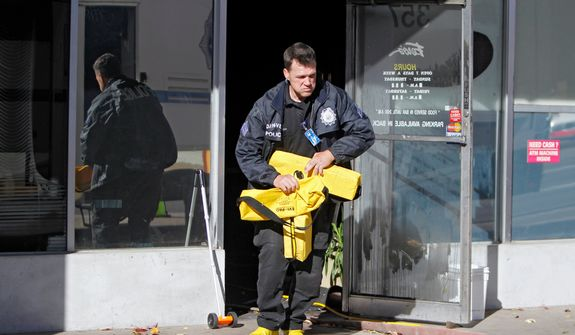 A police officer removes equipment at Fero's Bar and Grill in Denver on Wednesday, Oct. 17, 2012, where the bodies of a man and four woman were discovered after firefighters extinguished a fire at the bar early Wednesday morning. Police think the blaze was set to cover up their slayings. (AP Photo/Ed Andrieski)