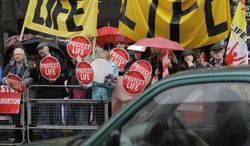 ** FILE ** Protesters opposed to abortion hold placards outside a Marie Stopes clinic in Belfast, Northern Ireland, on Thursday, Oct. 18, 2012. (AP Photo/Peter Morrison)
