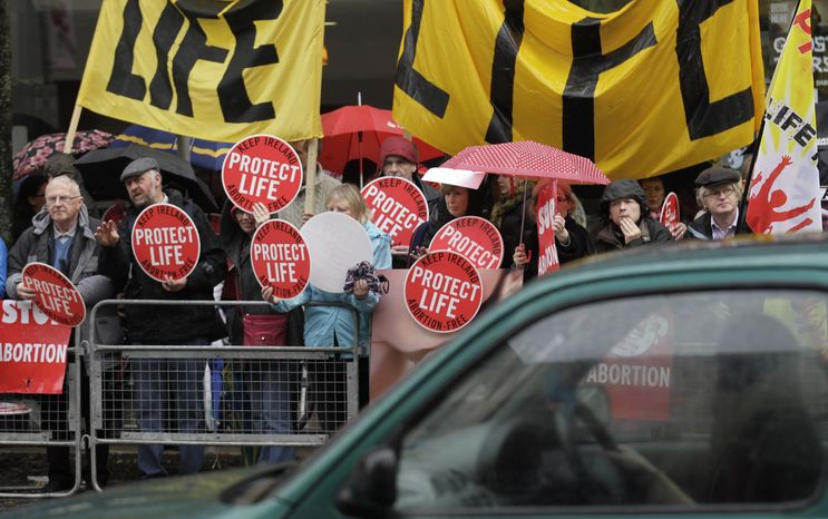 ** FILE ** Protesters opposed to abortion hold placards outside a Marie Stopes clinic in Belfast, Northern Ireland, on Thursday, Oct. 18